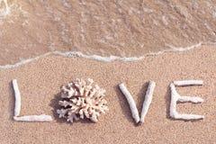 Lieben Sie das Wort, das von den Korallen auf einen tropischen Strand geschrieben wird Stockbilder