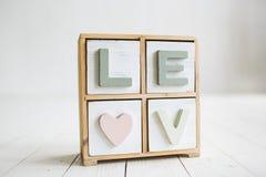 Lieben Sie dekorative Buchstaben auf dem weißen hölzernen Hintergrund Stockfoto