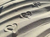 Lieben Sie die Herzen, die auf den Sand des Strandes gezeichnet werden Stockbilder