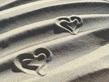 Lieben Sie die Herzen, die auf den Sand des Strandes gezeichnet werden Lizenzfreie Stockfotos