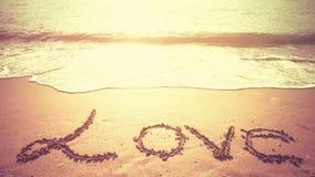 LIEBEN Sie die Mitteilung, die auf den Sand eines Strandes in Morgenzeit geschrieben wird Lizenzfreies Stockbild