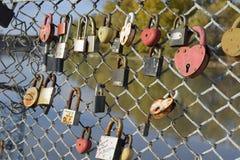 Lieben Sie die Verschlüsse, die von den Jungvermählten und von den Liebhabern auf dem Zaun nahe dem Fluss gehangen werden Ein Sym Stockbilder