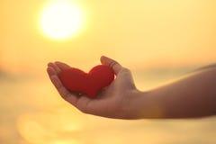 Lieben Sie für Valentinstag - zwei rote Herzen, die an das Seil zusammen mit Sonnenuntergang gehangen werden Lizenzfreies Stockbild