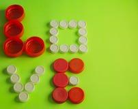 Lieben Sie geschrieben mit den roten und weißen Flaschenoberteilen auf einen grünen Hintergrund Stockfotos