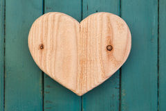Lieben Sie hölzernes Herz der Valentinsgrüße auf Türkis gemaltem Hintergrund Lizenzfreie Stockfotografie