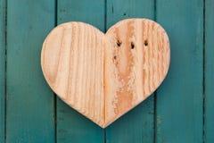 Lieben Sie hölzernes Herz der Valentinsgrüße auf Türkis gemaltem Hintergrund Lizenzfreies Stockfoto