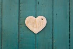 Lieben Sie hölzernes Herz der Valentinsgrüße auf Türkis gemaltem Hintergrund Lizenzfreie Stockbilder