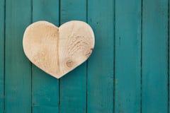 Lieben Sie hölzernes Herz der Valentinsgrüße auf Türkis gemaltem Hintergrund Stockfoto