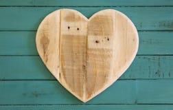 Lieben Sie hölzernes Herz der Valentinsgrüße auf Türkis gemaltem Hintergrund Lizenzfreie Stockfotos