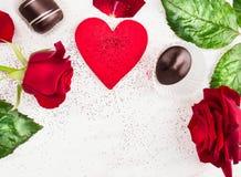 Lieben Sie Herzhintergrund mit roten Rosen und Schokoladenpralinen Stockfoto