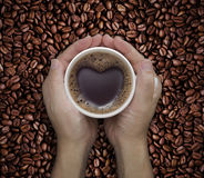 Lieben Sie Kaffeetasse in den Händen mit Herzform auf Bohne Stockfotos