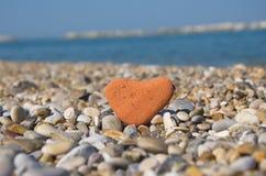 Lieben Sie Konzept mit einem Steinherzen auf Kieseln lizenzfreies stockbild