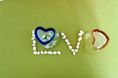 Lieben Sie Text vom Herzformglas und von wenigem Stein lizenzfreie stockbilder