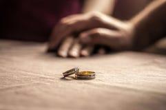Lieben Sie, Valentinsgruß ` s Tag und Hochzeitskonzept Zwei Eheringe mit den Mann- und Frauenhänden verwischt im Hintergrund Sele Lizenzfreie Stockfotos