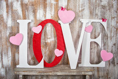 Lieben Sie Wort mit Herzen auf hölzernem Plankenhintergrund Stockbilder
