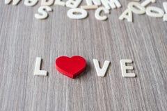 LIEBEN Sie Wort von hölzernen Alphabetbuchstaben mit der Frauenhand, die rote Herzform auf Tabellenhintergrund hält Romance, roma stockfoto
