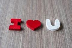 LIEBEN Sie Wort von hölzernen Alphabetbuchstaben mit der Frauenhand, die rote Herzform auf Tabellenhintergrund hält Romance, roma lizenzfreies stockbild