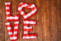 Lieben Sie Wort von roten Buchstaben des Plüschs auf hölzernem Hintergrund Lizenzfreie Stockbilder