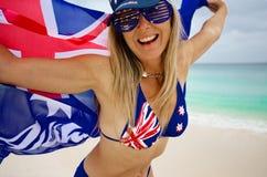 Liebende Frau des Spaßes, welche stolz die australische Flagge wellenartig bewegt stockfotografie