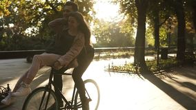 Liebende junge Paare haben den Spaß, der auf das gleiche Fahrrad Tätigkeit in der im Freien mit Sonnenhintergrundbeleuchtung auf  stock video
