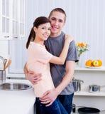 Liebende lächelnde Paare in der Küche Stockfotos