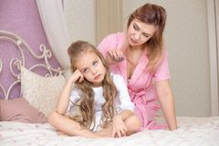 Liebende Mutter, die ihre traurige und mürrische Tochter tröstet lizenzfreie stockbilder