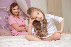 Liebende Mutter, die ihre traurige und mürrische Tochter tröstet lizenzfreies stockfoto