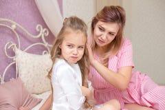 Liebende Mutter, die ihre traurige und mürrische Tochter tröstet stockbild