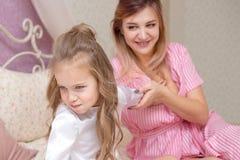 Liebende Mutter, die ihre traurige und mürrische Tochter tröstet lizenzfreie stockfotos