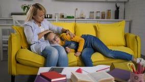 Liebende Mutter, die ihre umgekippte Tochter auf Sofa tröstet stock footage