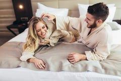 Liebende Paare in den Bademäntel, die auf Bett im Hotel sich entspannen stockfotos