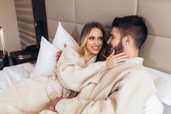 Liebende Paare in den Bademäntel, die auf Bett im Hotel sich entspannen stockfoto