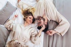 Liebende Paare in den Bademäntel, die auf Bett im Hotel sich entspannen lizenzfreies stockbild