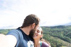 liebende Paare, die ein selfie beim Küssen in im Freien nehmen Freund mit einem Bart Familie, die zusammen reist stockfotos