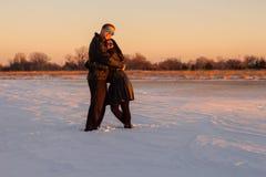Liebende Paare, die im Schnee umarmen stockbilder