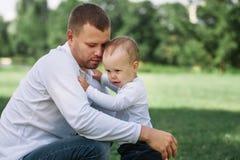 Liebende Vatergespräche zu seinem jungen Sohn beim draußen gehen lizenzfreie stockfotos