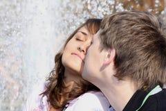 Liebende (verliebte) Paarküsse gegen einen Brunnen Stockfotografie