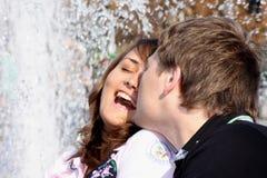 Liebende (verliebte) Paarküsse gegen einen Brunnen Stockbilder