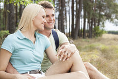 Liebende wandernde lächelnde Paare bei der Entspannung im Wald Stockbild