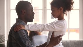 Liebender afrikanischer Vater, der wenig schwarzes Kindermädchen ausdrückt Sorgfalt umfasst stock footage