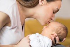 Liebender Mutter-Umarmungsbaby-Sohn und ihm Kuss auf Stirn geben lizenzfreie stockbilder