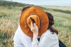 Liebendes Paar küsst das Schlagen hinter einem Hut lizenzfreie stockfotografie