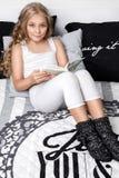 Liebenswürdiges junges schönes blondes Mädchen, kleine Prinzessin mit dem langen Haar und den blauen Augen, das Kind liegt im Bet Lizenzfreie Stockfotos