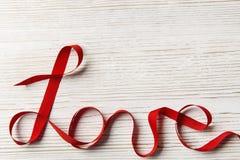 Liebes-Band-verdrehtes Wort, hölzerner Hintergrund getrennt auf weißem, selektivem Fokus Stockfoto