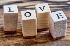 Liebes-glückliches Valentinsgruß-Tageskonzept Liebes-Stempel auf Weinlese Woden-Hintergrund Liebe geschrieben in hölzerne Blöcke Lizenzfreies Stockbild