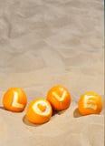 Liebes- und Ferienkonzept - die geschnitzte Aufschriftliebe auf den Orangen, liegend auf dem Sand Lizenzfreies Stockfoto