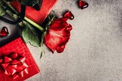 Liebes- und Valentinsgrußtagesgrußkarte mit roten Rosen, Geschenken und Herzen auf grauem Hintergrund, Draufsicht Stockfoto