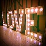Liebes-Zeichen-Wort-Glühlampen gegen Scheunen-Wand Stockfotografie