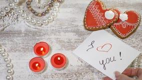 Liebesbeziehungen Saiint-Valentinstag Zwei heartshaped Ingwerplätzchen und brennende Kerzen auf hölzernem Hintergrund frau stock video footage