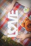 Liebesbriefe auf dem picnik mit den Händen eines Paares Lizenzfreie Stockbilder